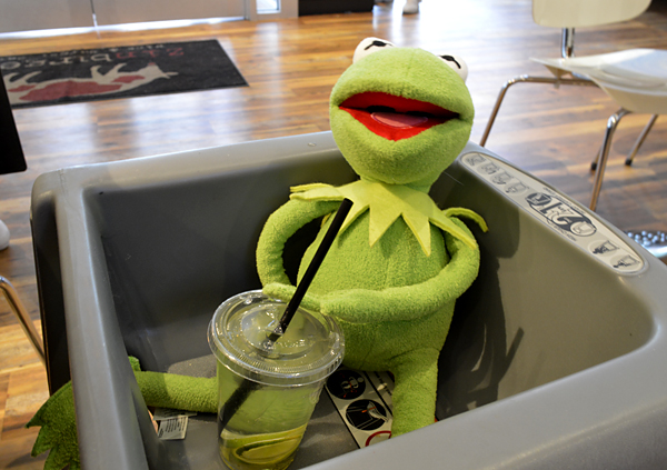 Kermit in a high chair enjoying seltzer and lime