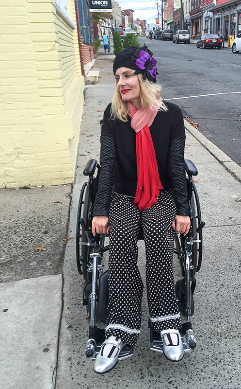 Pretty Cripple - wheelchair streetstyle wearing Prada Maryjanes, faux leather sweatshirt by Generation Love and lounge pants and custom made flapper hat.